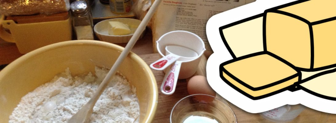 A photograph of a kitchen workspace with a bowl full of batter and a wooden mixing spoon, some measuring cups and an egg. On top of the photo is a clip art illustration of a stick of butter. 13sparrows