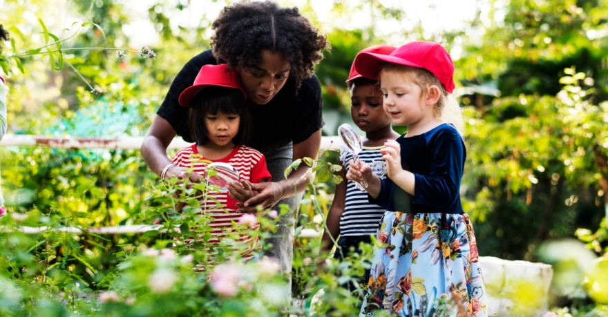 A photograph of a teacher guiding a young student using a magnifying glass on a plant in a garden while two other children watch.